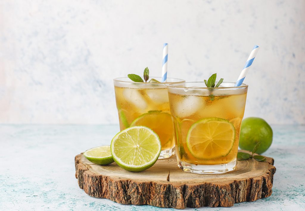 paper strawsIced tea with lime and ice on light background
